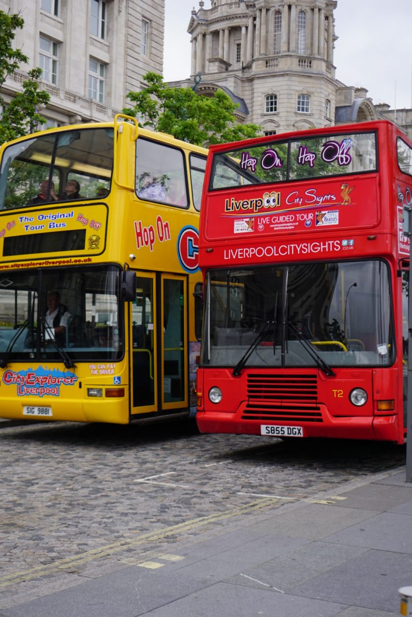 A red tour bus and a yellow tour bus in liverpool