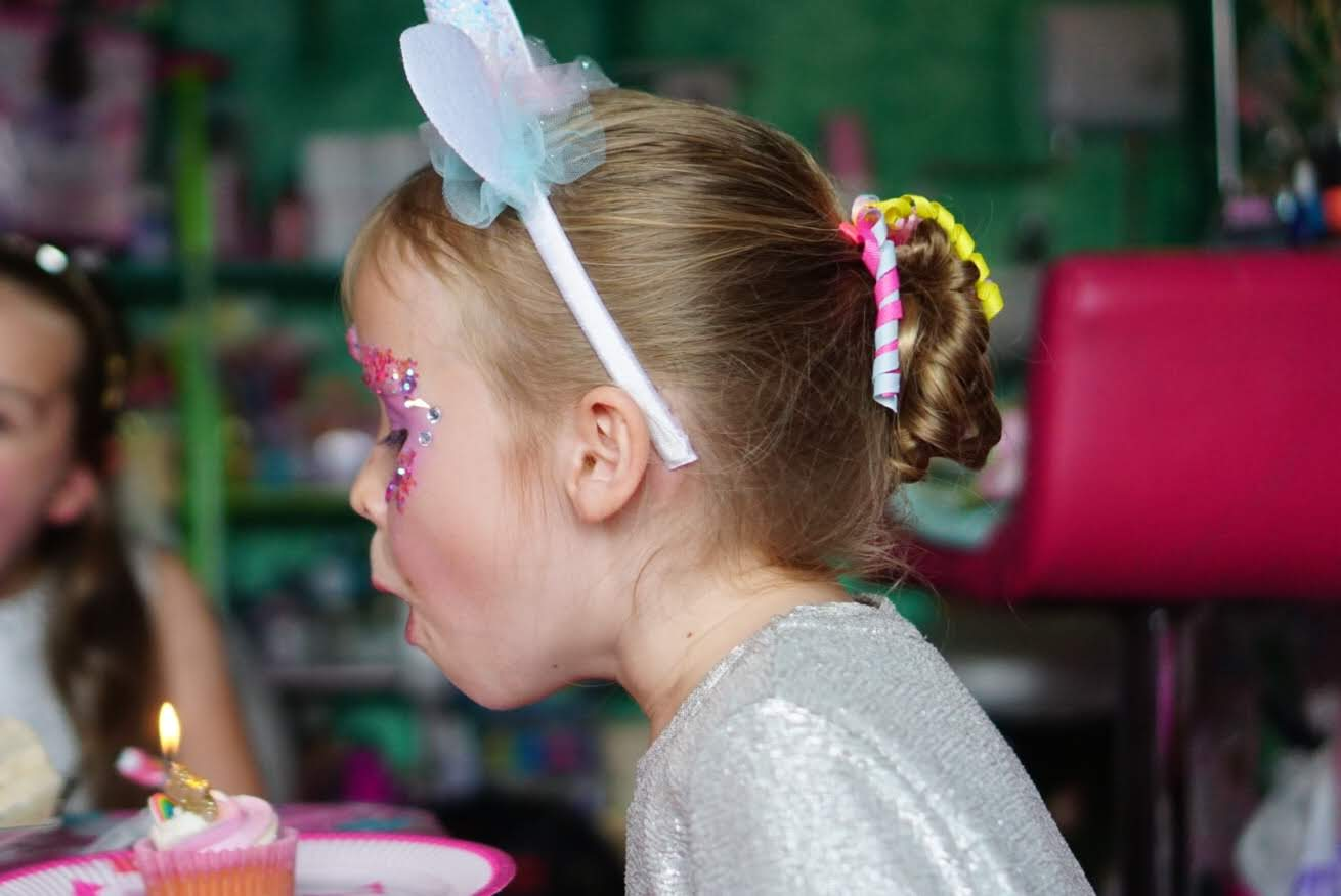 A little girl with sparkles on her face blowing out a candle.