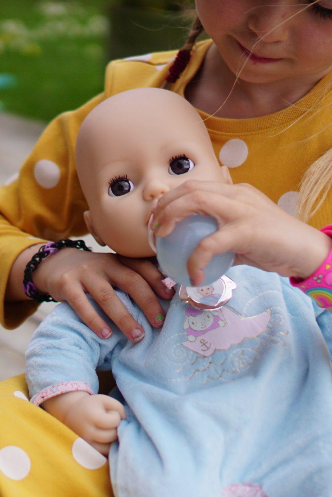 Girl feeding a Baby Alexander doll a bottle
