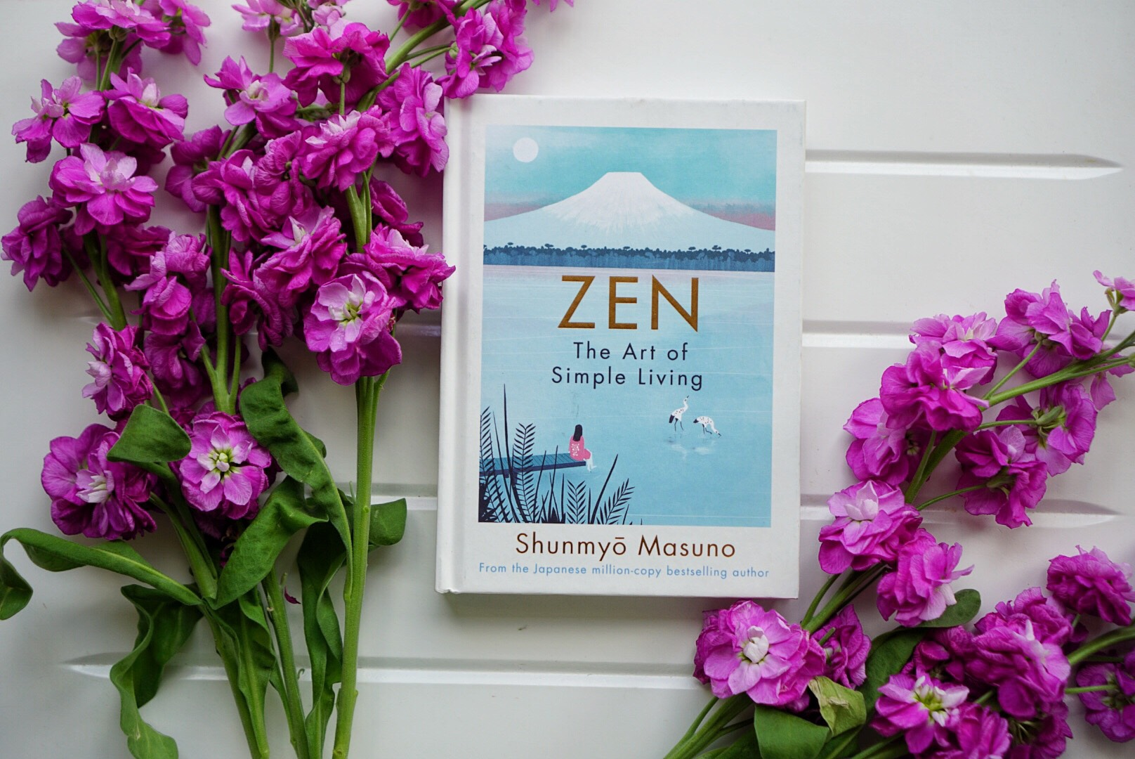 The book Zen The Art of Slow Living on a white table next to some flowers